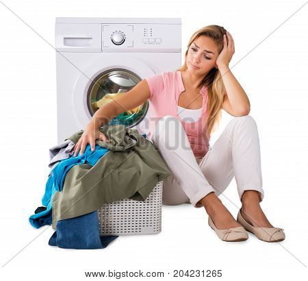 Worried Young Woman With Heap Of Laundry In Basket Sitting Near The Washing Machine