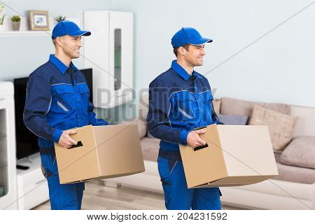Young Smiling Professional Movers In Uniform Delivering Cardboard Boxes In Living Room