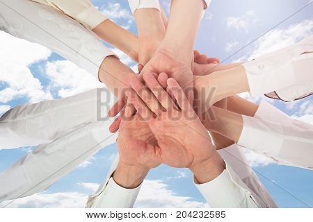 Low Angle View Of Multiracial Restaurant Staff In Uniform Stacking Hands