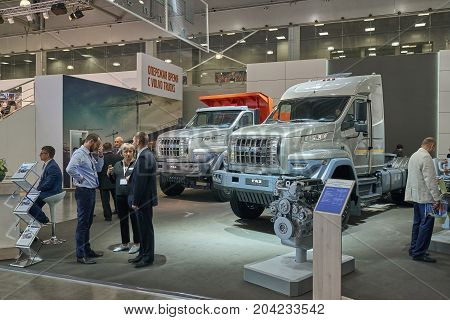 MOSCOW, SEP, 5, 2017: View on serial off-road URAL mud truck for hard to reach areas. Off road cargo trucks for civil military transportation. People on Commercial Transport Exhibition ComTrans-2017