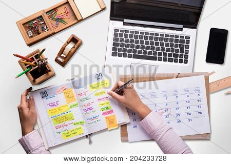 Businessperson Writing Schedule In Diary With Laptop And Mobile Phone On Desk