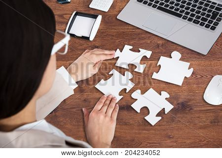 Close-up Of A Businesswoman's Hand Solving Jigsaw Puzzle In Office