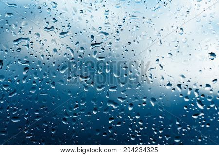 Rainy wet cold blue abstract eco seasonal natural blurred background with water drops