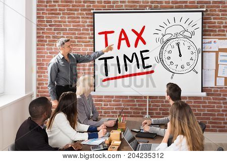 Man Giving Tax Time Presentation To Group Of People