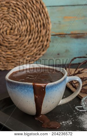 Delicious melted chocolate sauce in mug with whisk on table.