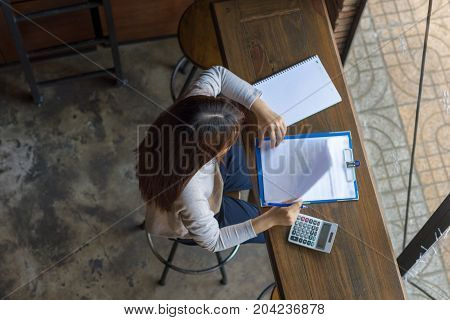 Young female working with a lot of reports and documents
