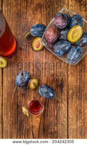 Plum Liqueur on rustic wooden background as close-up shot