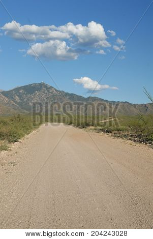 A gravel and dirt path leading into the mountains in southern Arizona with a blue sky and puffy white clouds.