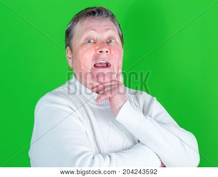 Strict Look Of Angry Senior Woman, Isolated Studio Portrait On Green Background