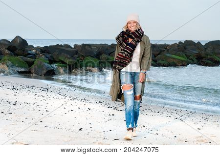 Beautiful Woman In Warm Coat And Cap Walking On The Beach In Autumn