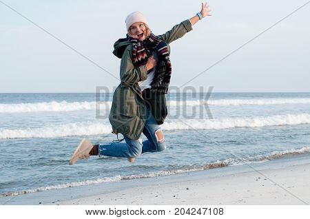 Happy Woman In Jackets And Warm Cap Jumping On The  Beach In Autumn