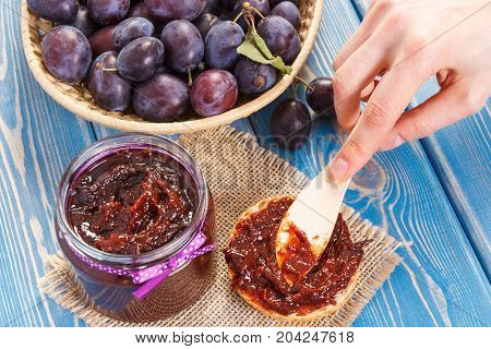 Hand Of Woman With Knife Preparing Sandwiches With Plum Marmalade Or Jam, Healthy Sweet Snack Concep