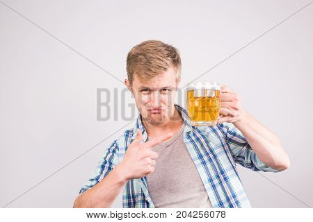 Happy young man holding and pointing on a beer mug.