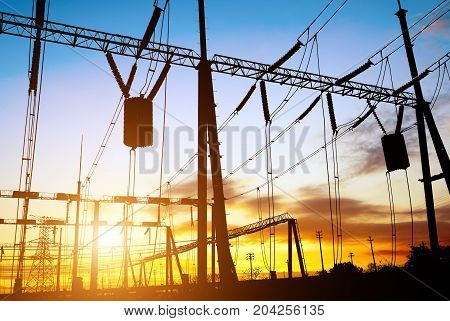 Substation lines and equipment silhouette at dusk.