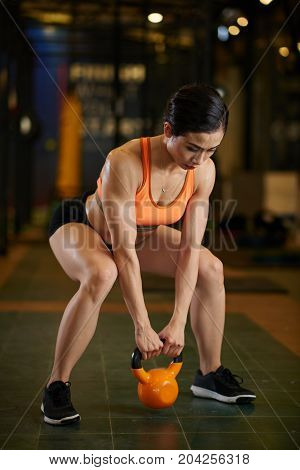 Vietnamese sporty woman doing squats with kettlebell