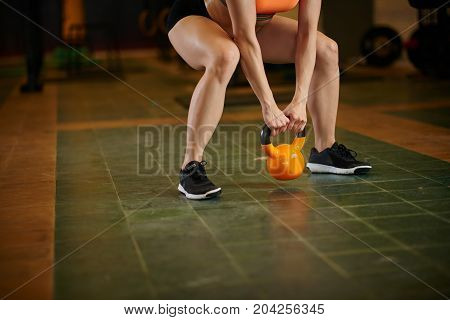 Cropped image of female athlete performing exercise with kettlebell
