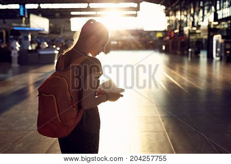 young woman in the hall of the airport terminal with a passport and boarding pass. silhouette of a woman in a bracing light. woman waiting for her flight on background blur airport check-In counters and passenger.