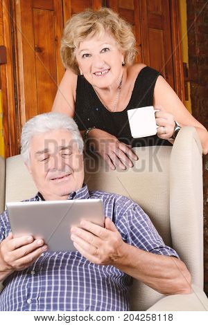 Portrait of an old couple using digital tablet sitting on couch. Indoors.