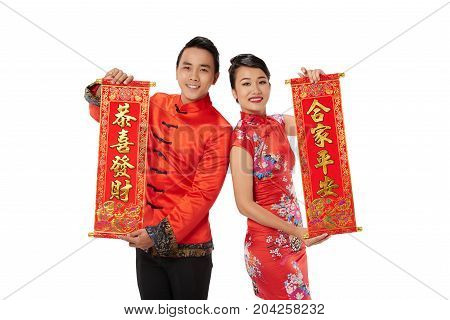 Cheerful Asian man and woman showing couplets written on red scrolls