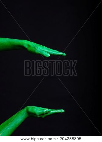 Hands of green color isolated on a black background.