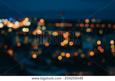 Blurred city lights against dark evening sky. Abstract background with urban bokeh
