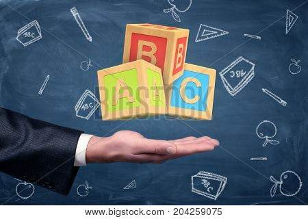 A businessman's hand turned palm up with big ABC blocks hovering above it. Education business. Management 101. Learning to work.