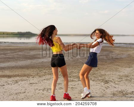Two girlfriend reel round circling in dance in the summer daisy. Summer field against blue sky with white clouds. Woman play outdoor in short stylish clothes. Friendship concept - happy young women.