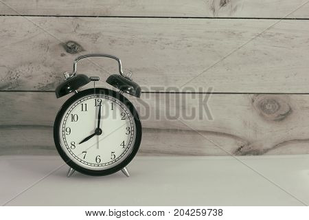 Retro alarm clock placed on white plate and wood in background. Time management concept.