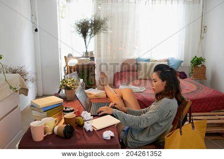 Asian university student doing homework at her tablet in dorm