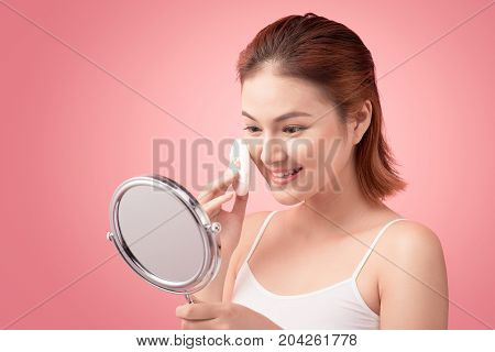 Young Lady Applying Blusher On Her Face With Powder Puff And Mirror, Skin Care Concept On Pink Backg
