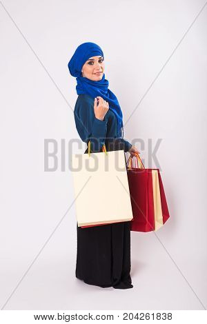 Happy young muslim woman with shopping bag on white background.