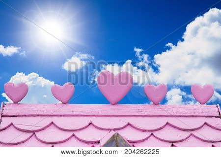 Love House Concept Closeup Wooden Home Roof Pink Color With Heart On Blue Sky Background