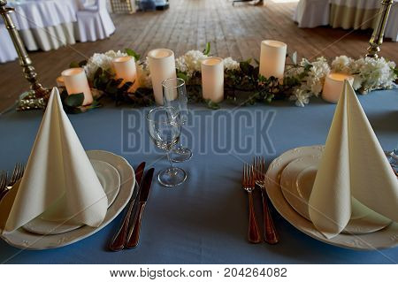 Serving wedding table. Starched white napkins , led candle and flowers on a blue tablecloth. The table of the newlyweds