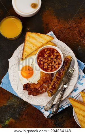 Traditional english breakfast with fried eggs, bacon, sausages, toasts and beans. Selective focus