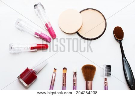 Top view of A collection of cosmetic beauty products arranged around a blank space on a white background.