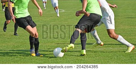 Men are playing soccer outdoors in summer