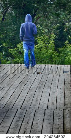 On the edge of the cliff. Step off the wooden bridge into the abyss. The last step down. The young man walks to the edge of the cliff. The old boards on the bridge.