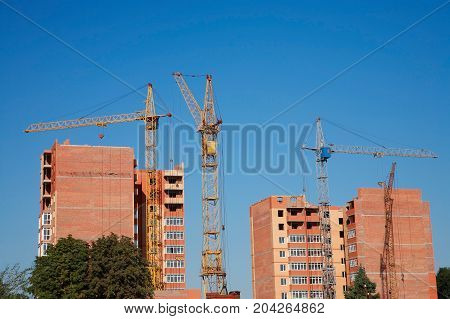 Construction site сonstruction cranes and under construction brick house against the sky