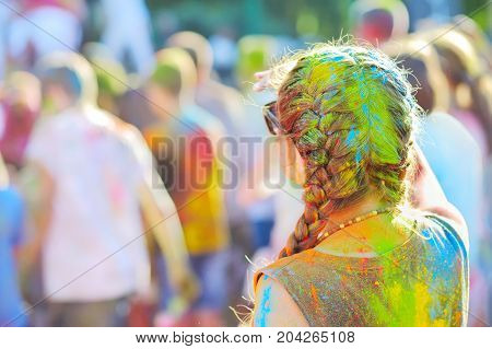 Color festival the girl with braids multi-colored paints view from back