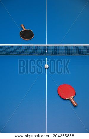Rackets for blue table tennis of red and black color and a ball on a tennis table view from above