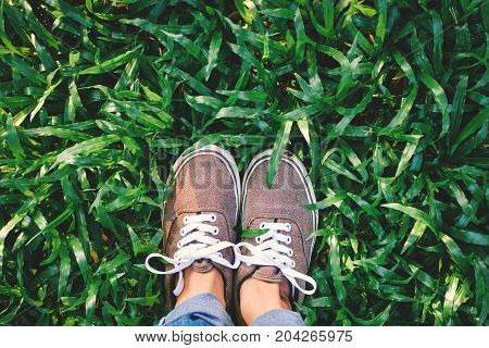 Top view hipster feet girl on green grass background Relax time on holiday