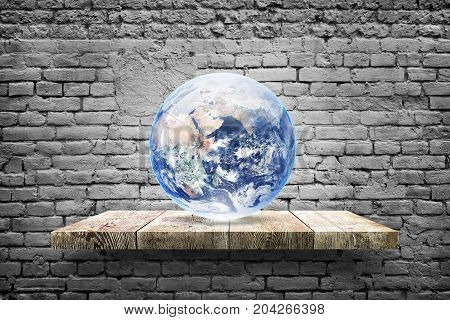 Illustration of  earth globe on wood shelf over white brick background. Elements of this image furnished by NASA