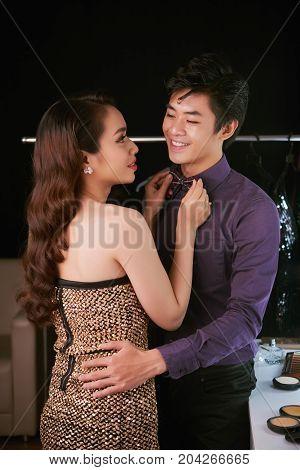 Beautiful Vietnamese woman adjusting bowtie of her boyfriend