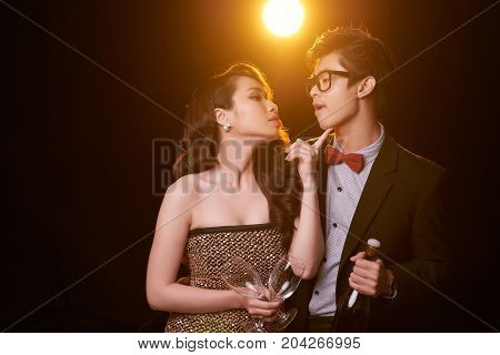 Beautiful Vietnamese boyfriend and girlfriend in love holding champagne and looking at each other