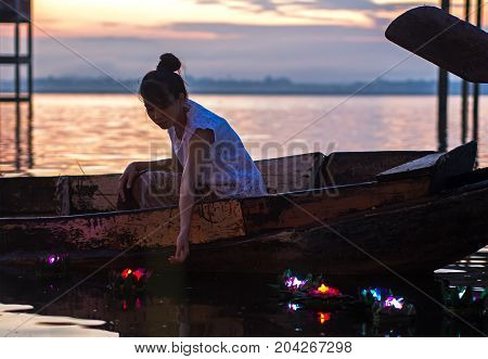 Asian women Loy Kratong Festival on the fishing boat in the reservior Travel Thailand.