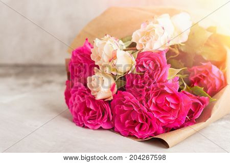 Pink roses bouquet  in sunny beams. Shallow depth of field. Toned image