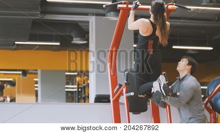 Fitness-club - young woman performs Pull-Ups with male coach - rear view, close up view