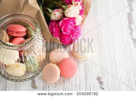 French macarons cookies and flowers over white wooden background. Mothers day or Valentines day greeting card