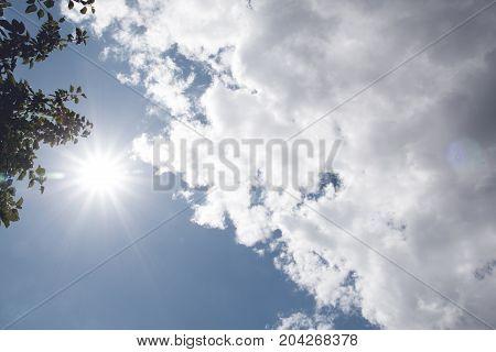 sun and cumulus white clouds against a beautiful blue sky, bizarre patterns