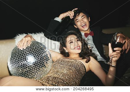 Laughing young couple lying on sofa with wine and disco ball
